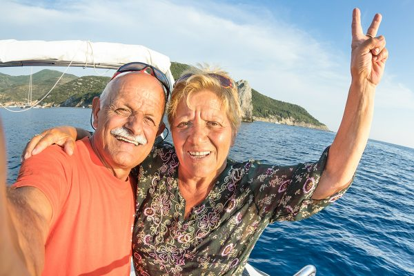 Adventurous senior couple taking selfie at Giglio Island on luxury speedboat - Active elderly travel lifestyle concept on happy tour moment - Retired people around world - Warm afternoon color tones